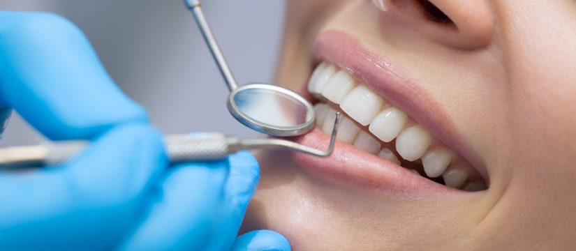 dentist cleaning patients teeth